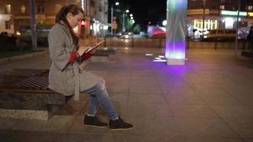 uma jovem na praça e usando tablet digital.