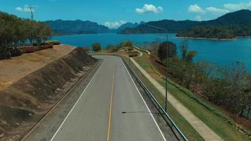 aéreo: drone de ascensão da estrada em direção ao lago.