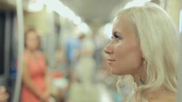 Thoughtful blonde wearing a blue dress standing in a subway car
