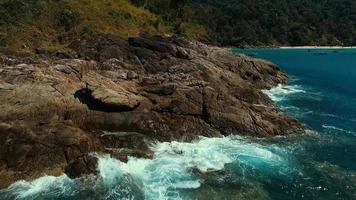 aérea: voar perto das rochas na praia com barcos de cauda longa. video