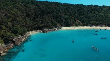 Aerial: Beautiful white sand beach with long tail boats.
