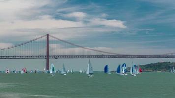 pesci vela sul fiume Tago con ponte sospeso 25 aprile su sfondo timelapse video