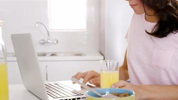mulher tomando seu café da manhã e usando seu laptop