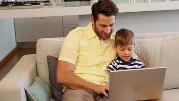 padre e figlio utilizzando laptop sul divano