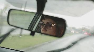 uma mulher de óculos dirigindo na chuva. video