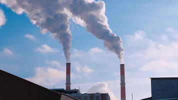 Riesige Rauchwolken aus Industriekaminen schließen den blauen Himmel
