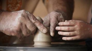 Hands of old potter and young pupil video