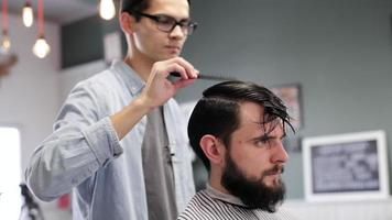 Peluquero peinando el cabello del cliente antes del corte de pelo en una peluquería video