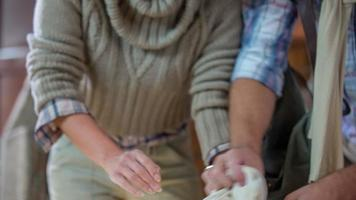 Lovely couple kneading the dough to make a bread