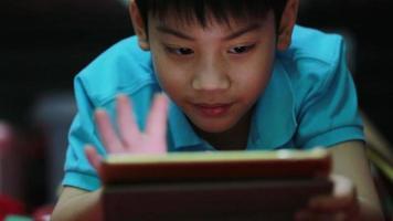 garotinho asiático jogando no jogo do tablet video