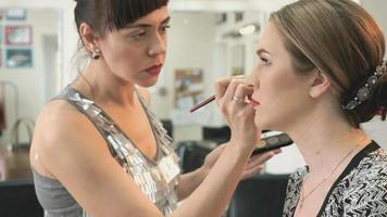 maquiador fazendo maquiagem para modelo estilosa
