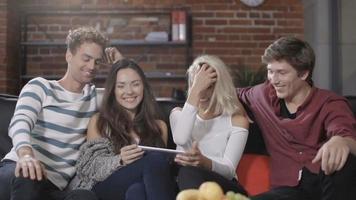 gruppo di giovani amici felici seduti su un divano e utilizzando il computer tablet.