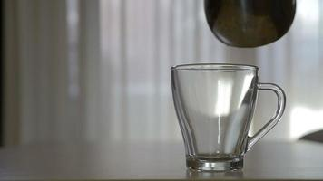 Pouring hot coffee in a transparent mug in the morning in slow motion video