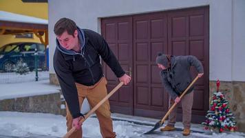 Two men have shovelled most of the snow in front of the house