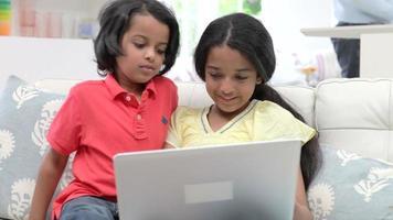 crianças usando laptop enquanto estão sentadas no sofá em casa