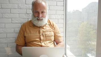 homem sênior atencioso e encantado trabalhando em seu laptop