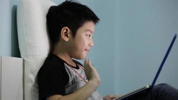 menino bonito asiático assistindo e falando no computador portátil.