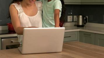 felice madre e figlia con laptop in cucina video