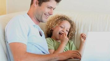 padre con suo figlio in ginocchio utilizzando un computer portatile