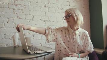 mulher bonita jovem feliz trabalhando em seu laptop no café
