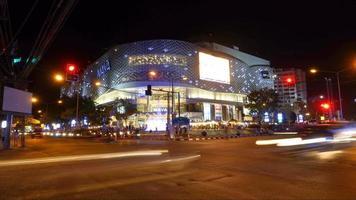 Chiangmai, Tailândia - 23 de novembro de 2016: lapso de tempo do trânsito intenso na interseção noturna em frente ao shopping center de maya, um marco histórico na província de Chiangmai, Tailândia.