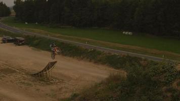 rallentatore aereo: motociclista di motocross estremo che salta nessun trucco footer al tramonto