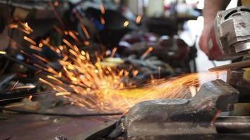 Trabajador amoladora muele metal en el taller