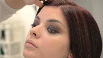 modelo olhando para cima enquanto maquiador usa base pincel