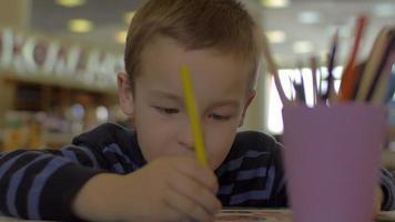 à la table assis un petit garçon et dessine avec des crayons de couleur