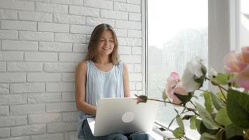 Hermosa niña caucásica feliz enviando mensajes de texto en su computadora portátil