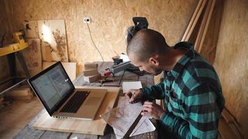Jeune charpentier audacieux avec dessin de moustache dans son atelier