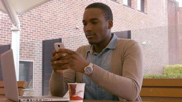 giovane seduto utilizzando smartphone video
