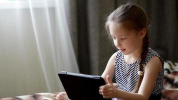 menina criança brincando em um computador tablet