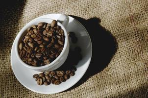 Taza llena de granos de café tostados en saco de arpillera de productores foto