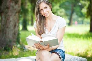 Young beautiful woman reading a book in the park