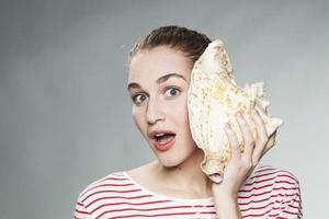 amazed young woman with shell to ear for exotic vacation