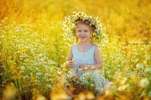 Girl among camomiles photo