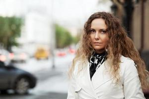 Beautiful woman in white on the city street photo