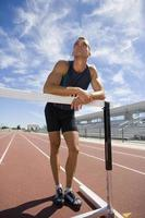 Male athlete resting arms on hurdle, low angle view