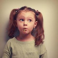 chica divertida comiendo dulces con ojos grandes y sorprendentes. foto