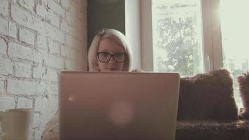 Feliz hermosa joven trabajando en su computadora portátil en el café