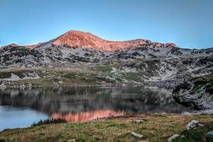 Sunrise on a mountain peak near a lake
