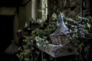 Clear glass bottle in brown wicker basket