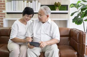 Happy senior Asian couple using tablet