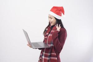 Young smiling woman wearing red Santa Claus hat making video call