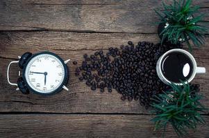 reloj despertador, taza de café y granos de café en el escritorio