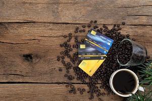 tarjetas de crédito y granos de café en el escritorio foto