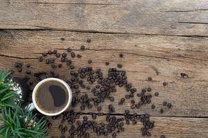taza de café y granos de café en la mesa de madera foto