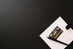 cuaderno, bolígrafo y tarjeta de crédito en el escritorio