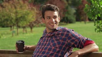 uomo con caffè su una panchina nel parco